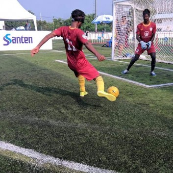 A blind player strikes the ball from outside the goalkeepers box towards the goal of the sighted keeper