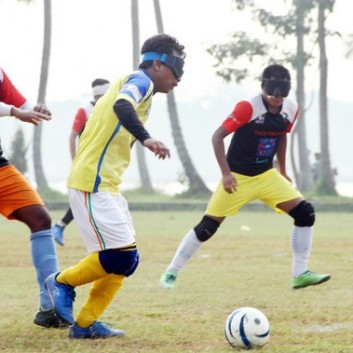 Blind footballer Anthony Samuel takes the ball past an opponent in a training match